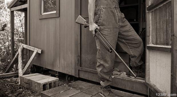Armed man defending his house from door
