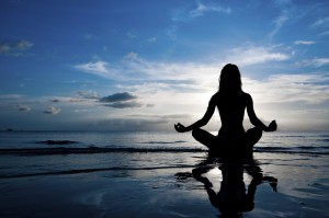 Woman in lotus position on shore at sunset