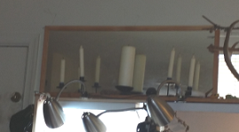 Candles on shelf in front of mirror