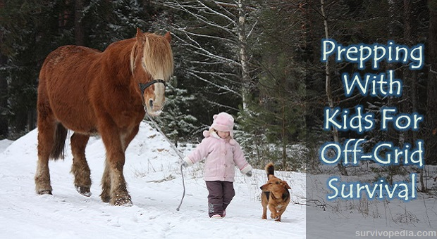 Little girl dressed in pink leading a horse and a dog in snow